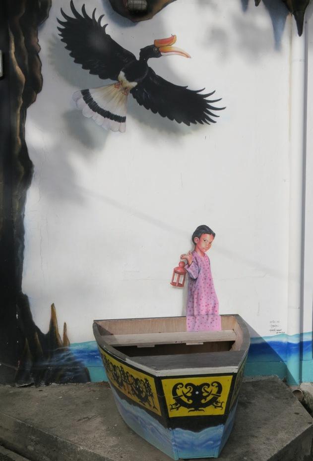 Malay girl in sampan and hornbill