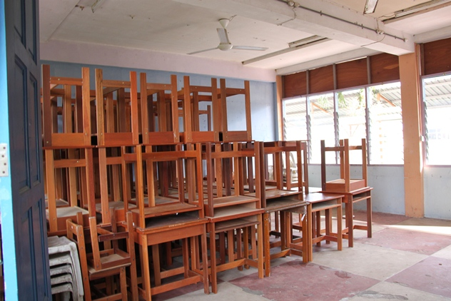 An unused classroom with deeks and chairs piled up at the backs