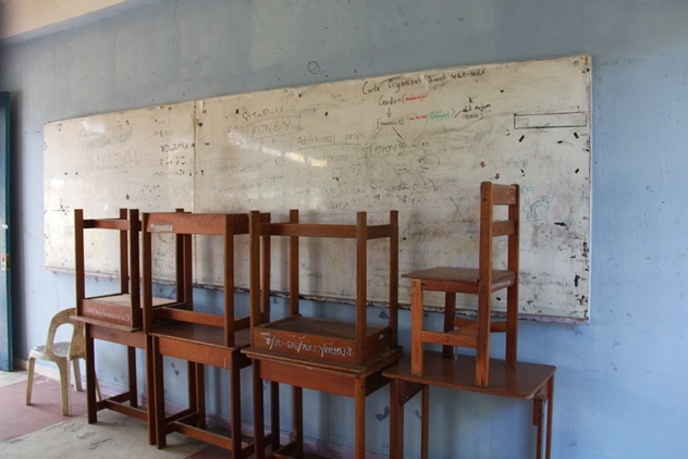 An unused classroom with deesks and chairs piled up at the front