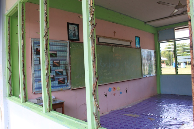 A classroom with missing window panes