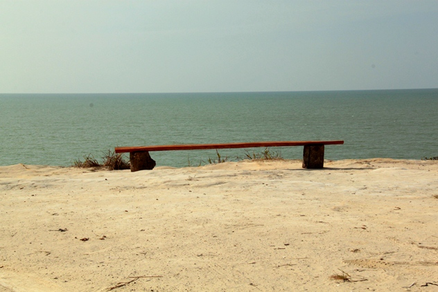 A bench overlooking the sea at the top of a cliff near the car park area