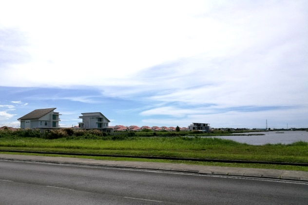 The lake and nice houses on the left side of the road