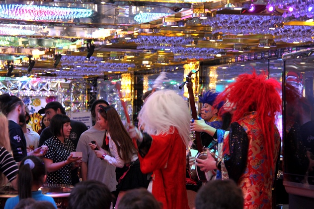 A trio dressed in kabuki-like costumes played wild music as patrons downed their sake