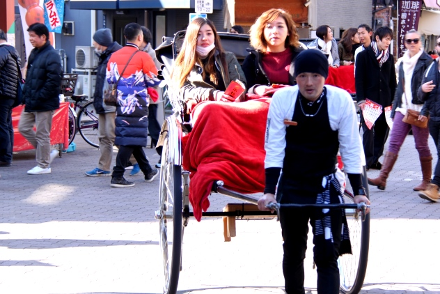 A Japanese rickshaw puller and his female customers