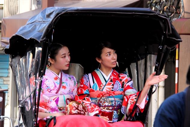 Two Japanese women in kimono on a rickshaw