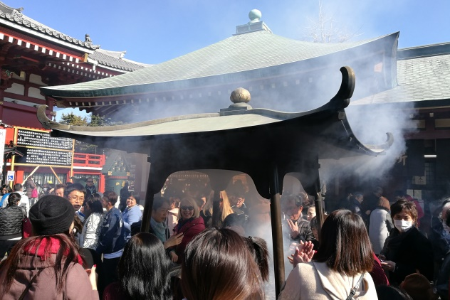 People crowding around an incense burner