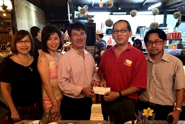 Kenny Goh handing over his cheque to Charles Leh
